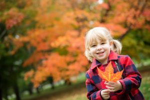 young girl, holding fall leaf