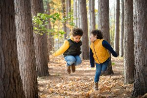 young boys jumping in leaves